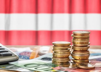 Euro banknotes and coins in front of the national flag of Austria