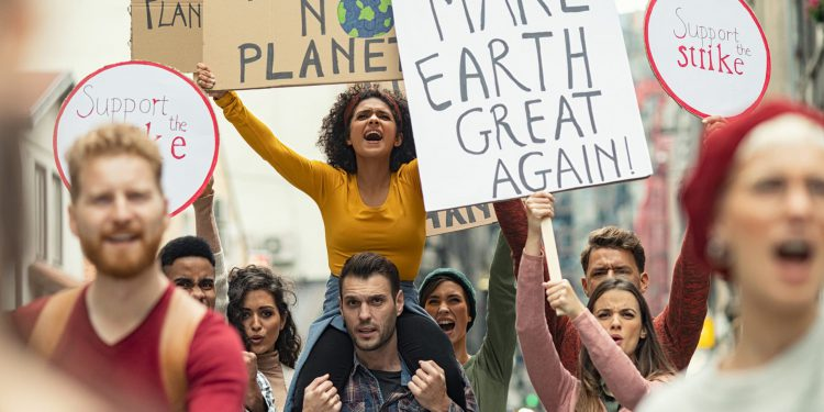 Group of young people demonstrate against climate change. Angry women and men strike with boards and signs in support of our planet. Group of activists protest and march to save the planet.